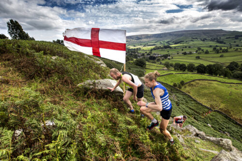 A woman in blue reaches the England flag on a fell race