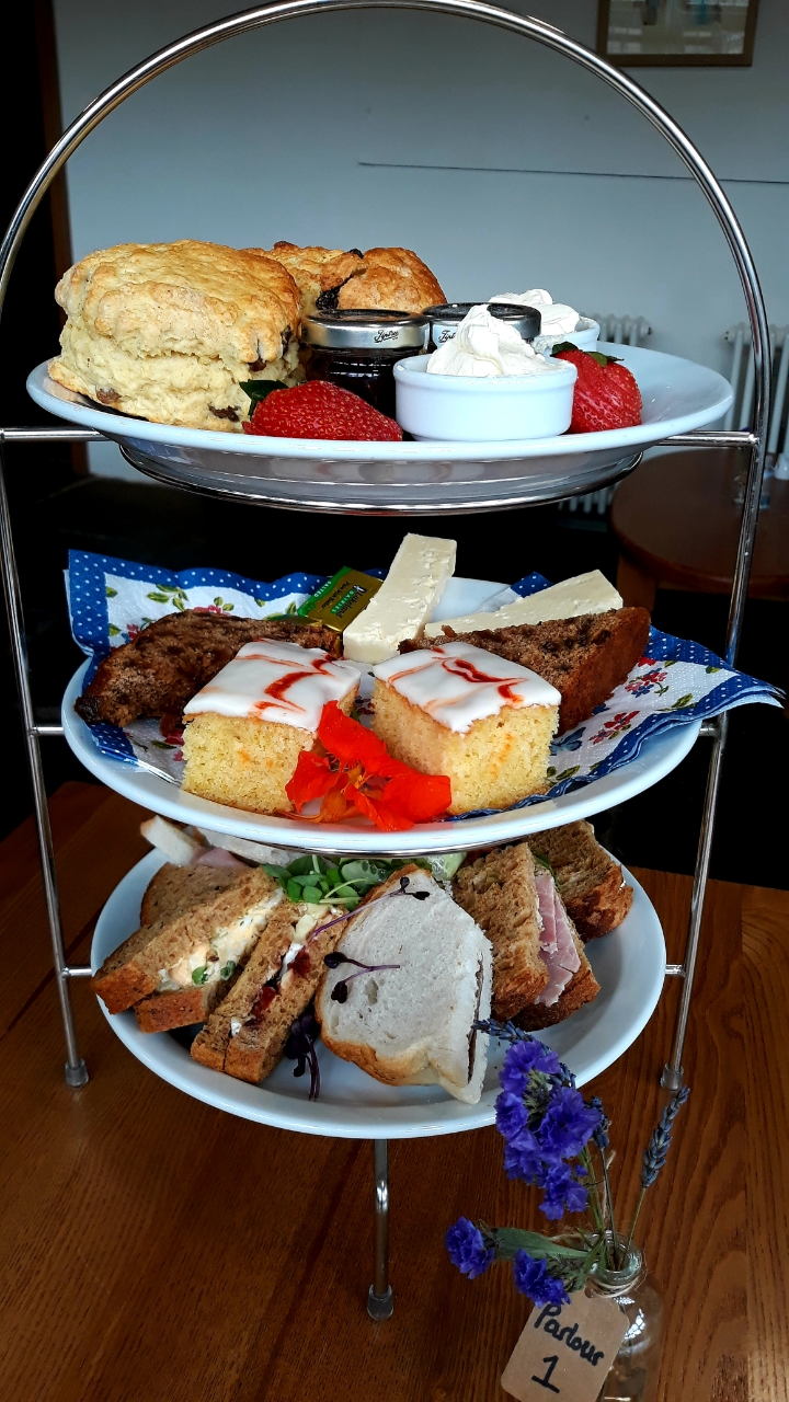 A three tiered cake stand featuring a scone, sandwiches and cakes
