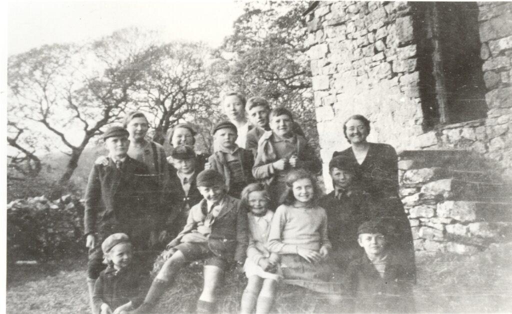Black and white photo of 15 smiling evacuees