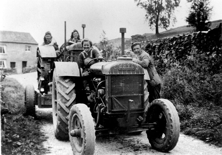Black and white photo of women driving two tractors