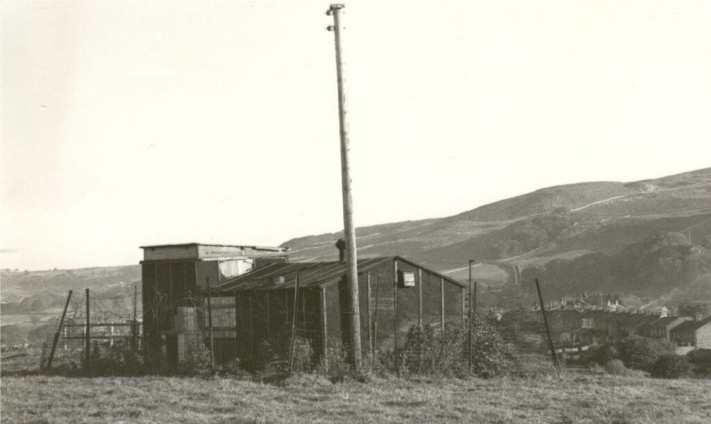 A black and white photo of a temporary structure with a tall white mast