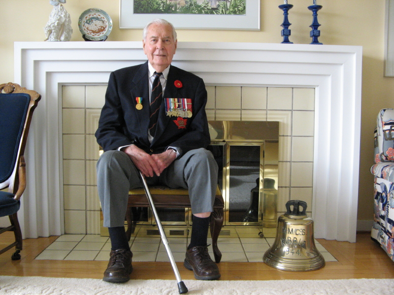 Colour photo of an old man wearing his military jacket and medals. On his right is the Ribble's bell
