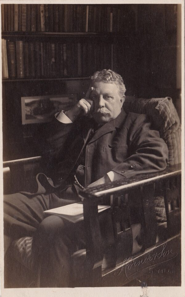 Black and white photo of Alfred Neave Brayshaw sitting down in a wooden chair. He has a hand to his temple.