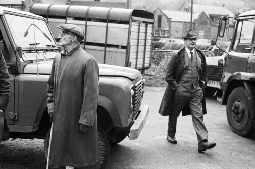 Black and white photo of two farmers in front of Land Rovers and a trailer from 1986