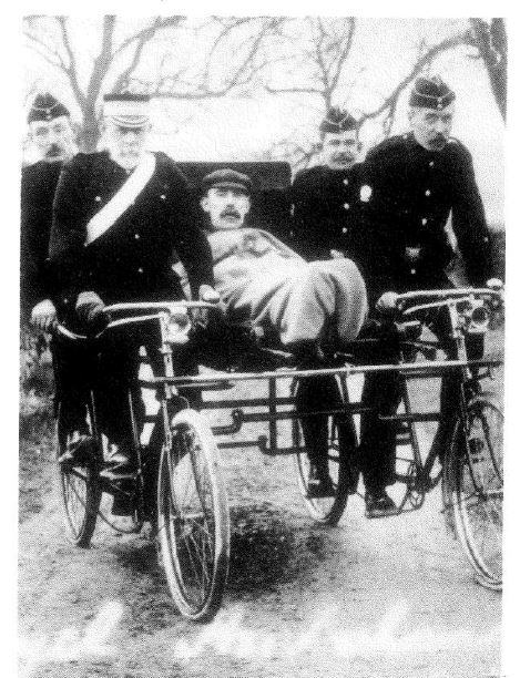 Black and white photo of five men supporting a buggy ambulance. A fifth man, wrapped in a blanket, rides on the buggy.